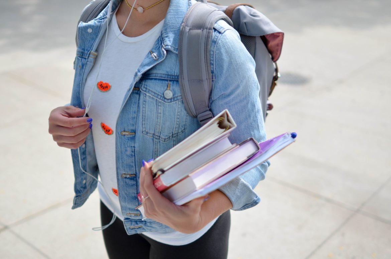 une personne portant un sac à dos et des livres dans la main gauche