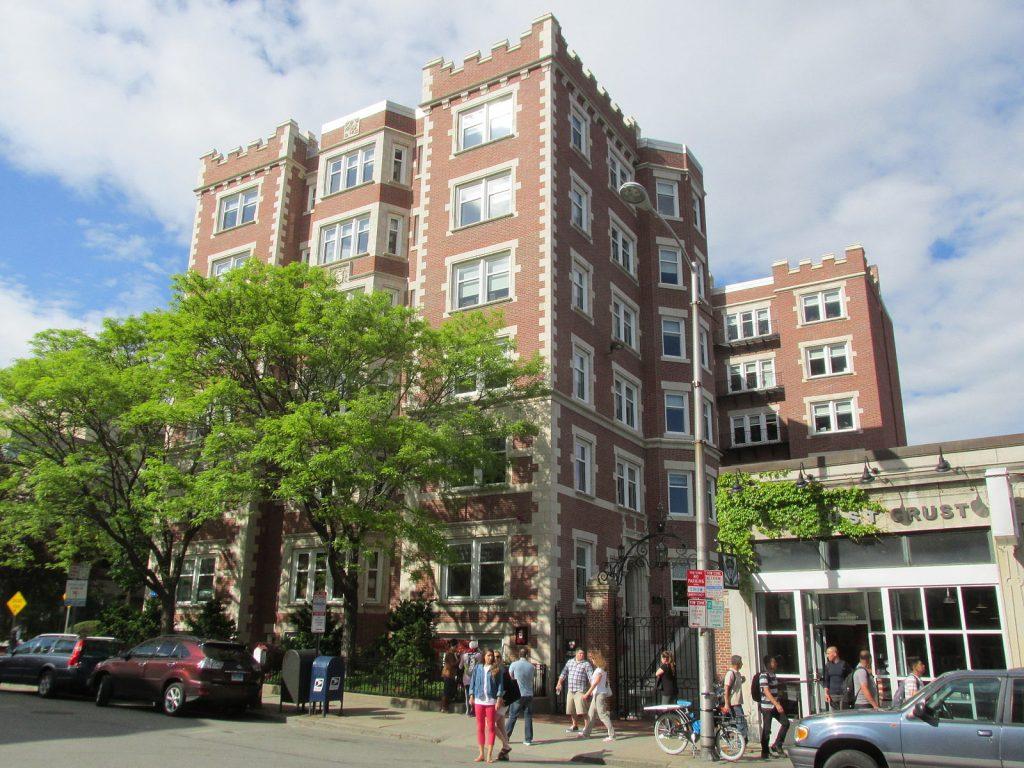 Un grand bâtiment en brique rouge typique à Harvard et à Boston. Devant le bâtiment, quelques personnes marchent sur le trottoir.