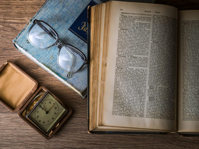De gauche à droite, un cadran ancien, une paire de lunettes de vue et des livres anciens